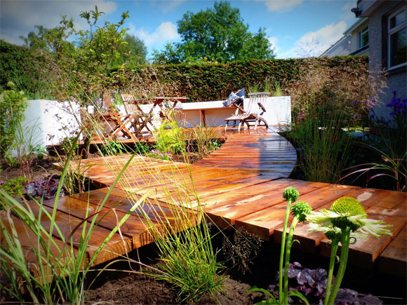 A contemporary boardwalk and bespoke deck with in-built seating in a garden in Bridge of Allan. Designed and built by Vialii
