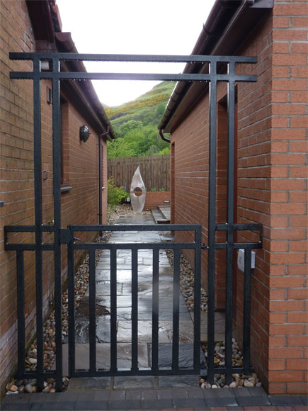 A Japanese-style bespoke gate creates a mood and the bespoke sculpture at the end of the path provides a focal point and encourages the journey into the garden