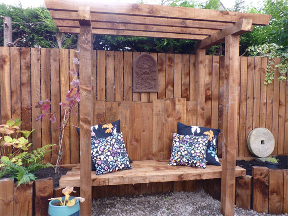 A bespoke arbour can be a lovely central feature of a garden]