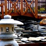 A Japanese lantern, water feature and koi bridge set the mood in this garden