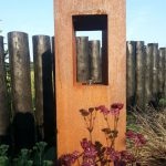 An oil lantern made from rusted metal is softened by planting