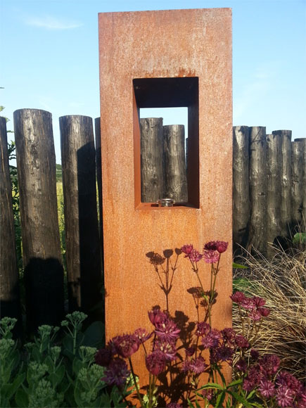 An oil lantern made from rusted metal is softened by planting and is perfect garden focal points