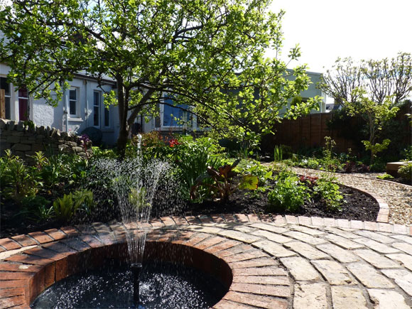 A beautiful water feature set into a patio creates a wonderful focal point at the end of the curving path