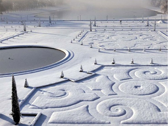 The empty flower beds reveal their intricate patterns when coated with snow