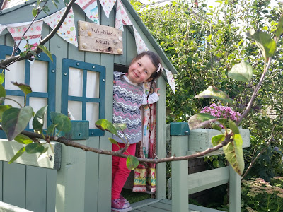 The new playhouse is tucked in the border between two apple trees
