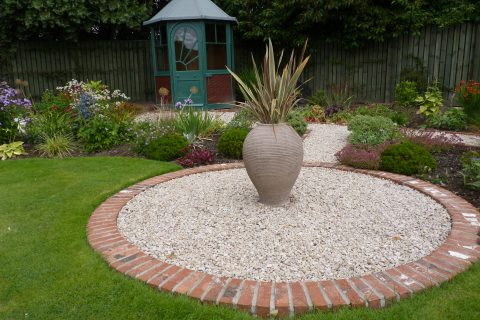 Feature pot in a gravel circle with the Art Deco summerhouse beyond