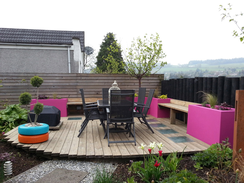 Bright pink, rendered raised beds provides planting space around the deck