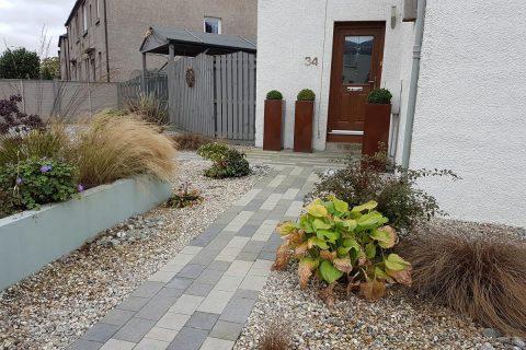 New bronze effect planters flank the door