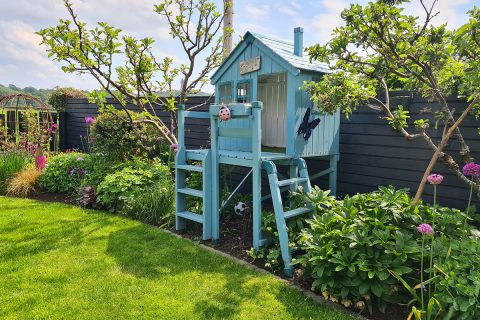The playhouse nestles between the apple trees
