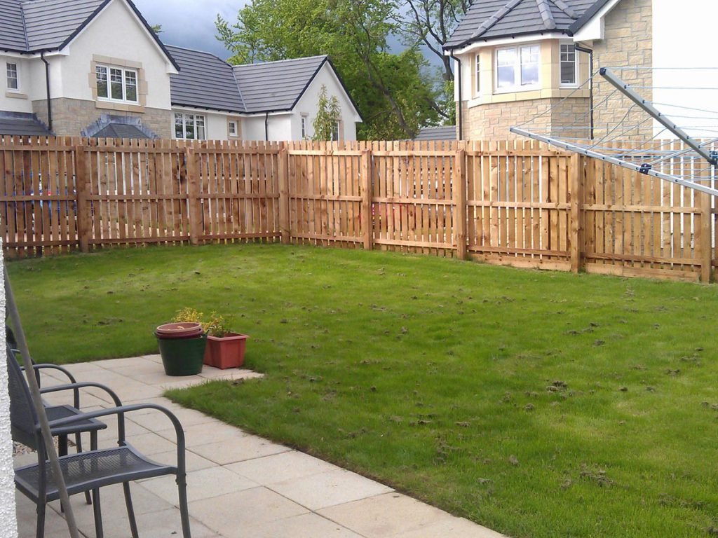 Before: single slatted fence and some grass