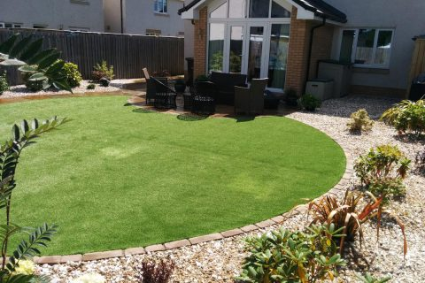 Artificial grass edged in setts