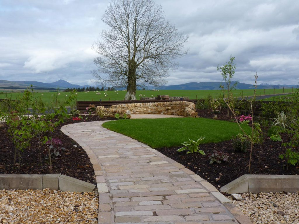 After: a cobbled path leads to a new patio with dry stone wall