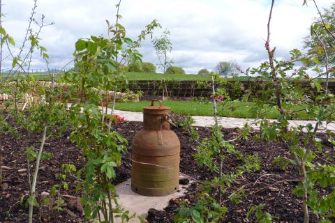 A dairy churn is an appropriate curio in the garden of an old dairy steading