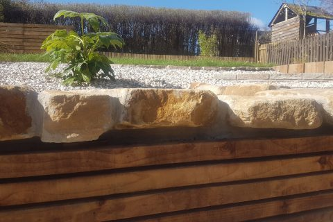 The new retaining wall clad in timber, topped in sandstone