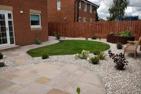 The new sandstone patio creates a lovely place to relax