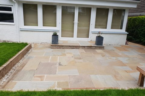 The new sandstone patio creates a lovely space for entertaining