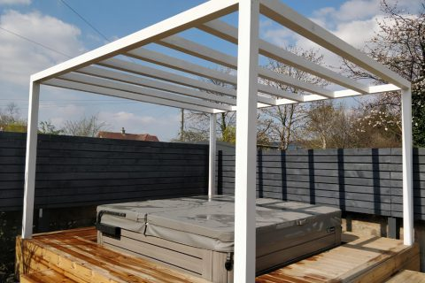 The white pergola makes a real statement above the hot tub