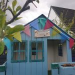 The playhouse bedecked in its upcyled garden bunting