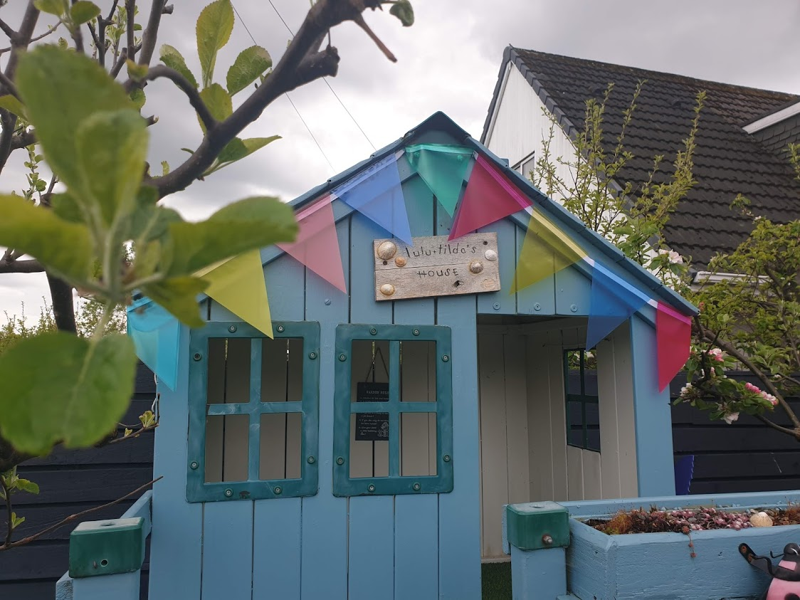 The playhouse bedecked in its upcycled garden bunting