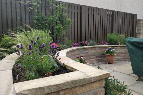 The new sandstone wall with planting