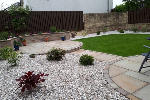 A sandstone path links the two new patios