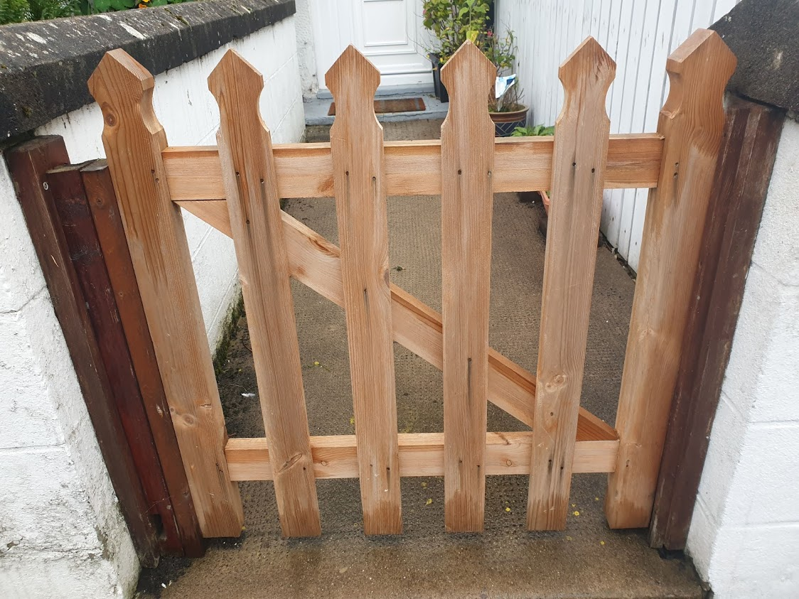 This simple picket style gate is an attractive entrance to the garden