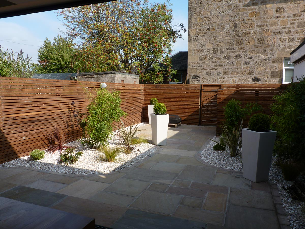 Tall stone planters create a contemporary look to tie in with the garden design and new house extension