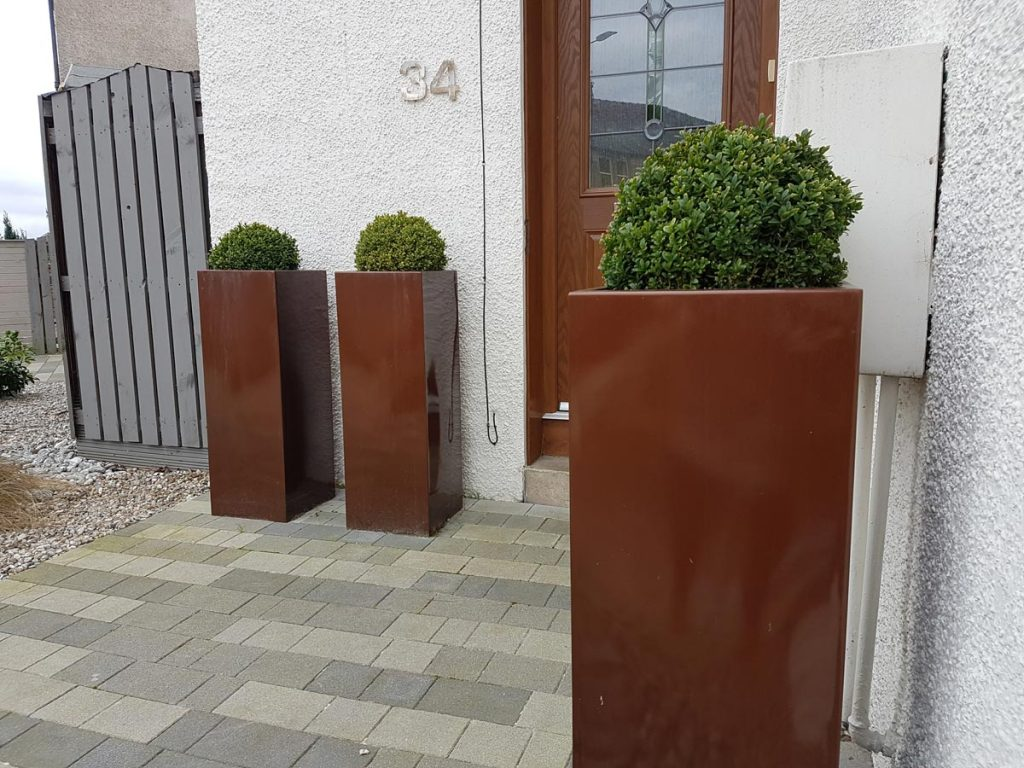 Rectangular copper planters create a warm welcome