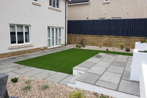 Modern paving complements the new artificial grass